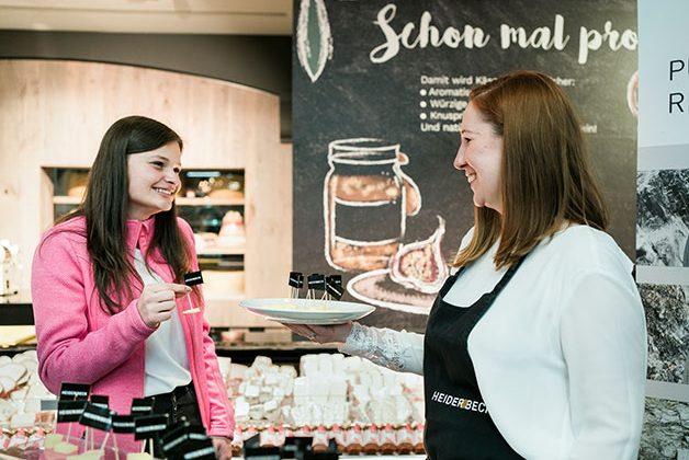 Werbedame verkauft Käse an Kundin im Supermarkt