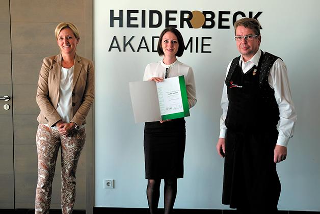 Larisa Krausel präsentiert ihr Diplom als Diplom Käsesommeliere. Links steht Christina Nussbaumer, rechts steht Hanspeter Chiste
