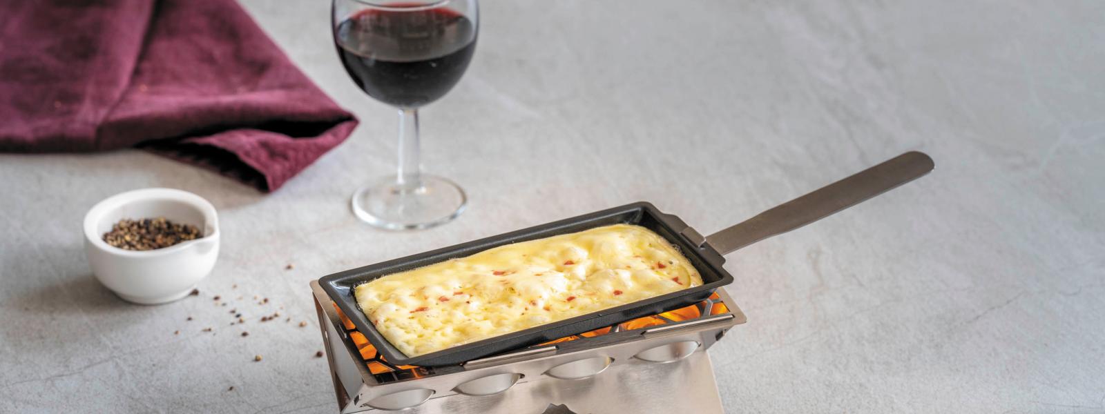 Ein Raclette Stöfchen brät Raclette, im Hintergrund ein Glas Rotwein und Pfefferkörner