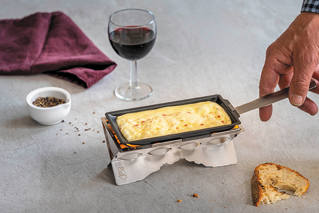 Ein Raclette Stöfchen brät Raclette, im Hintergrund ein Glas Rotwein und eine Serviette, flankiert von Pfefferkörnern