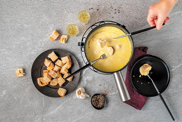 Seiler Raclette Pfannen mit geschmolzenem Käse. Ein Mann sticht mit Brot mit einer Raclette Gabel in den Käse