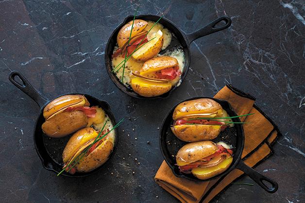 drei Pfannen mit Ofenkartoffeln und geschmolzenem Käse