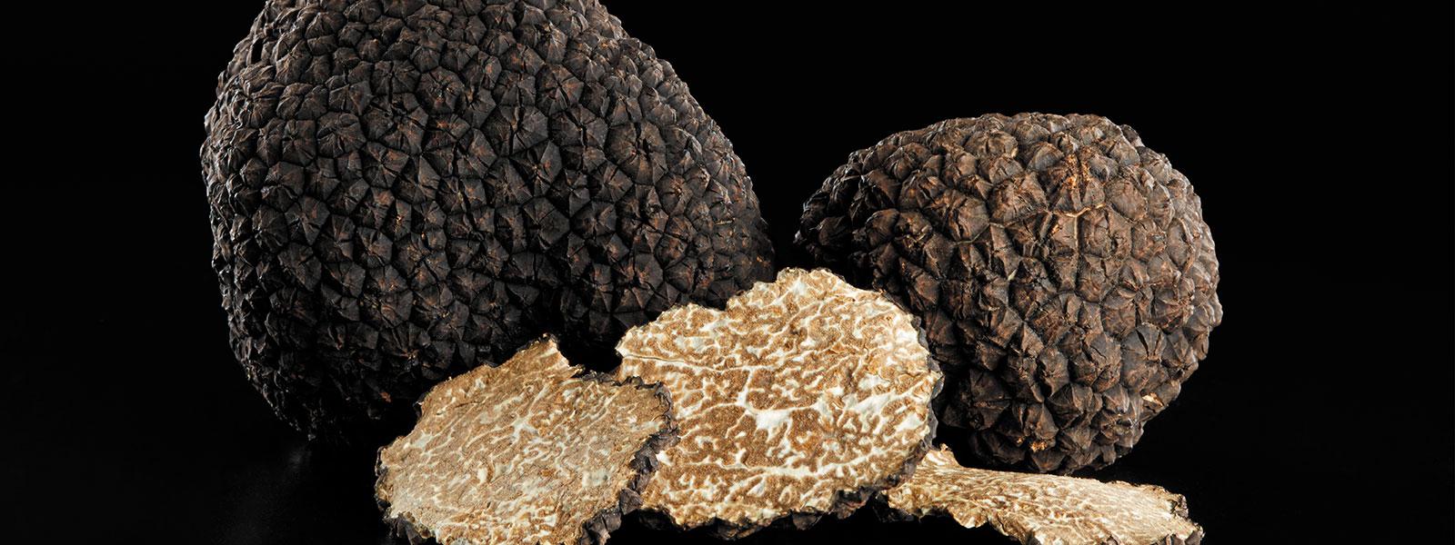 Trüffelknollen mit Trüffelstückchen auf schwarzem Hintergrund